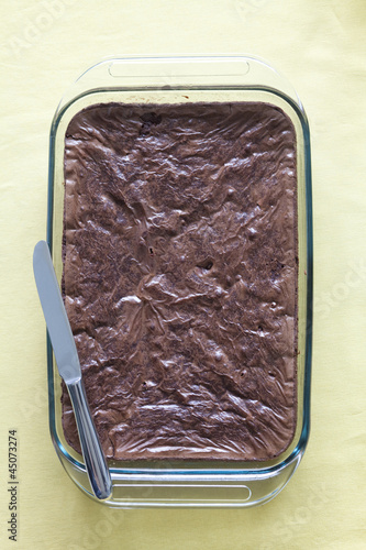 Chocolate cake in serving dish with knife