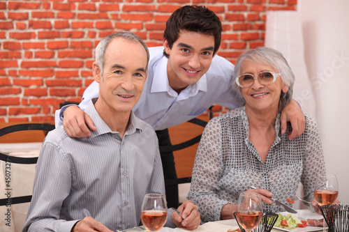 Elderly couple and grandson in restaurant