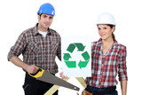 Man and woman stood with saw and recycling logo