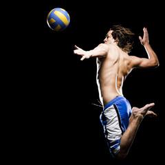 Studio shot of man jumping to hit soccer ball