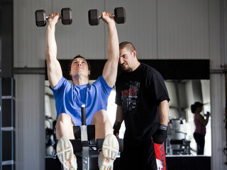 Instructor assisting man exercising in gym