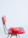 """Red whoopie cushion on red spotted chair, studio shot"""