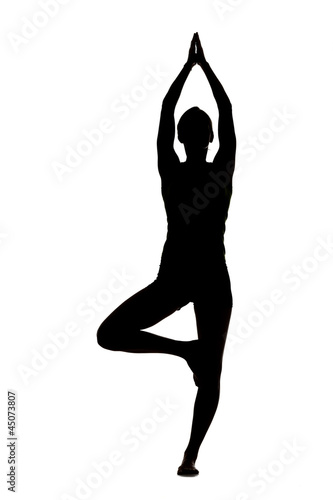"""USA, Utah, Orem, Silhouette of woman standing in tree pose against white background"""