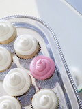 """Cupcakes with frosting on silver tray, close-up, elevated view"""