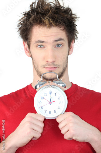 young guy with swollen eyes showing alarm clock