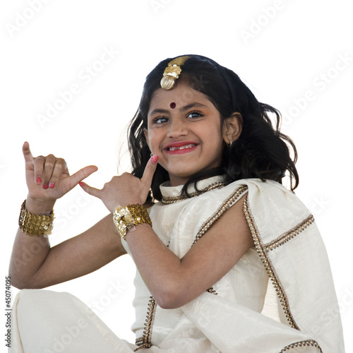 """Girl (8-9) wearing traditional sari performing figures from indian traditional dance, studio shot"""