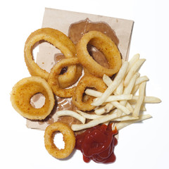 """Onion rings and french fries with ketchup on paper bag, view from above, studio shot"""