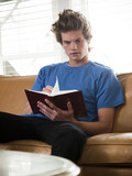 """USA, Utah, Provo, young man reading book on sofa"""