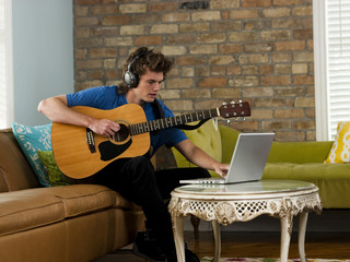 """USA, Utah, Provo, young man playing guitar, using laptop in living room"""