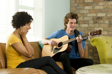 """""""USA, Utah, Provo, young man playing guitar with young woman covering ears"""""""