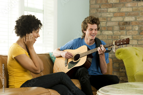 """USA, Utah, Provo, young man playing guitar with young woman covering ears"""