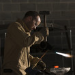 """USA, Utah, Orem, man welding with hammer and blowtorch in workshop"""