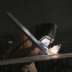 """USA, Utah, Orem, man soldering metal in workshop"""
