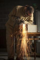 """""""USA, Utah, Orem, man welding metal in workshop"""""""