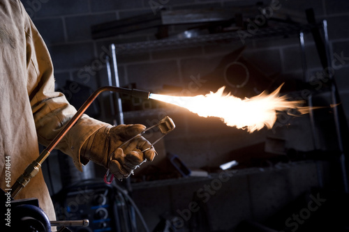 """USA, Utah, Orem, male welder with blowtorch in workshop"""