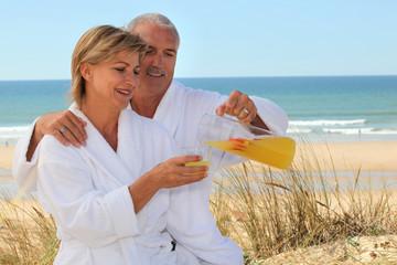 Couple in bathrobes on the beach