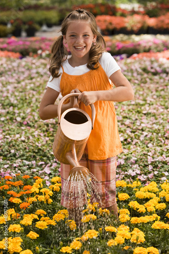 """USA, Utah, Salem, portrait of girl (8-9) watering flowers"""