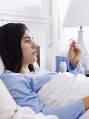 """Orem, Utah, USA, young ill woman l in bed looking at thermometer"""