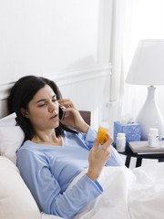 """Orem, Utah, USA, young ill woman in bed looking at pill bottle and talking on the phone"""