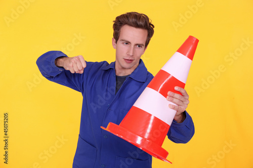 man hitting a traffic cone