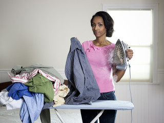 """Orem, Utah, USA, mid adult woman ironing"""