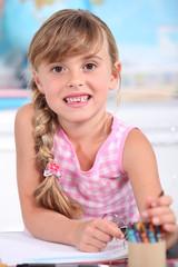 A cute little girl in her classroom.