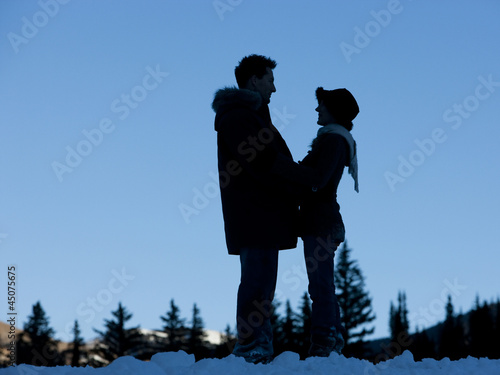 """USA, Utah, Big Cottonwood Canyon, couple standing face to face in snow"""