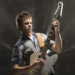 """""""Young man playing bass guitar, studio shot"""""""