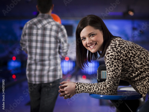 """USA, Utah, American Fork, young woman in a bowling club looking at camera"""