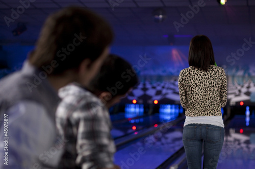 """USA, Utah, American Fork, rear view of girl standing in bowling alley"""