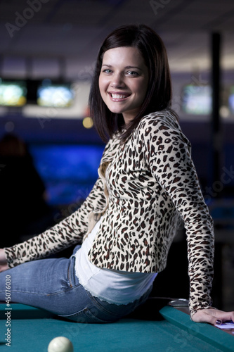 """USA, Utah, American Fork, young woman sitting on pool table and smiling"""