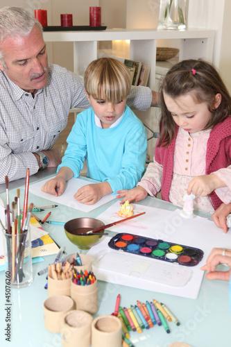 Man watching grandchildren paint