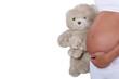A pregnant woman holding a teddy bear.