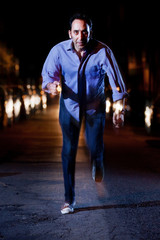 Man running away at night in the middle of a street