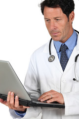 Doctor in a white coat and stethoscope with a laptop computer