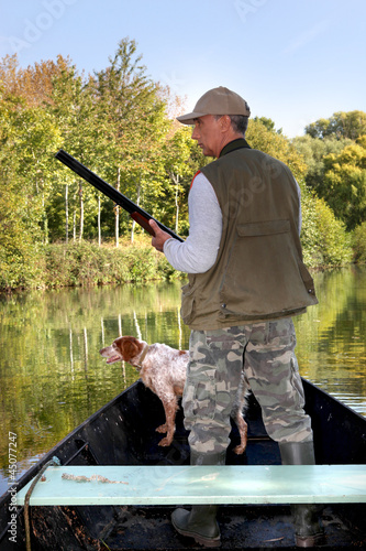 Hunter on boat with dog