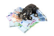 broken retro car model laying over banknotes