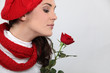 Woman in knitted hat smelling rose