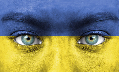 Human face painted with flag of Ukraine