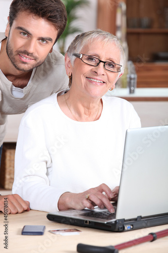 Young man helping senior woman with a laptop computer