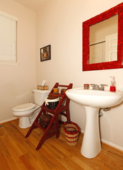 Small bathroom with sink and toilet and hardwood floor.