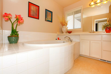 Bathroom with large round white tub and cabinets
