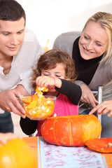 Young family carving hallowe'en pumpkins