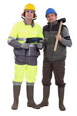Two workers with drill and hammer
