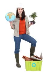 Female builder holding globe and plant