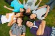 Six teenage friends lying on the grass and having fun