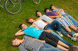 Teenage friends lying on the grass after riding bicycles