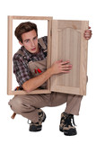 a young carpenter showing a piece of furniture