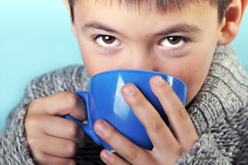 The boy in sweater with cup