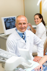 Mature dental surgeon in office with assistant